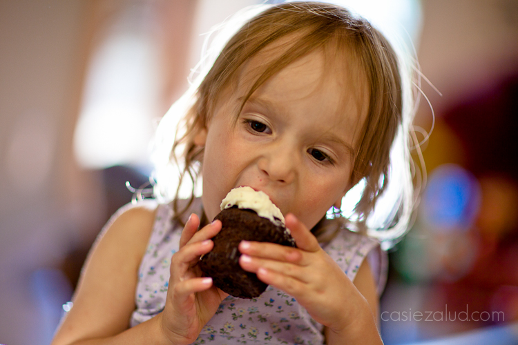 a girl taking an enormous bite from a cupcake