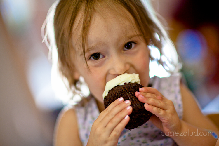 a girl trying to take an enormous bite of a cupcake