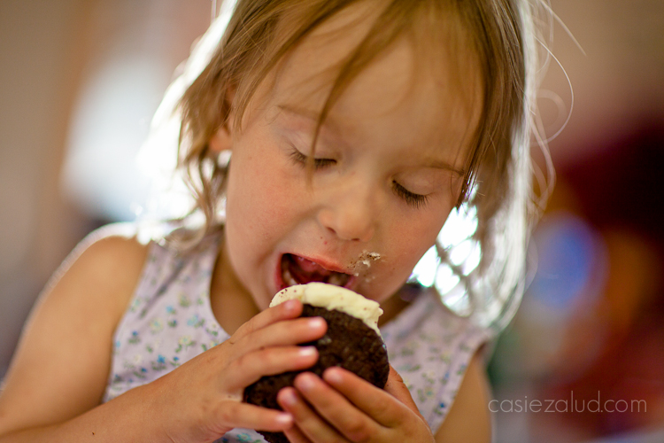 a girl eating a cupcake passionatly