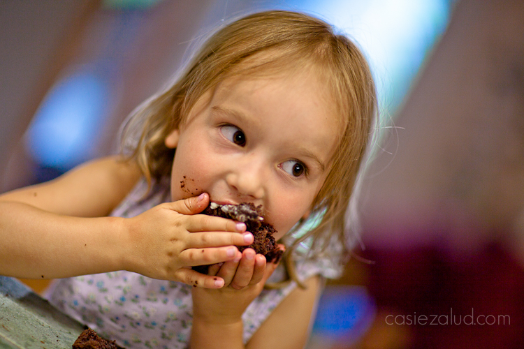 a girl trying to finish a cupcake by shoving the remains in her mouth