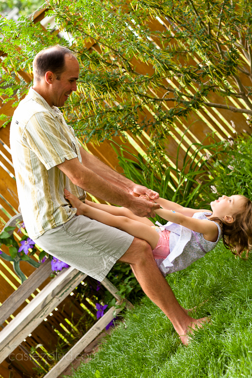 3 year old girl climbing on her dad to do a flip