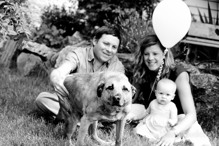 family in grass with balloon and dog