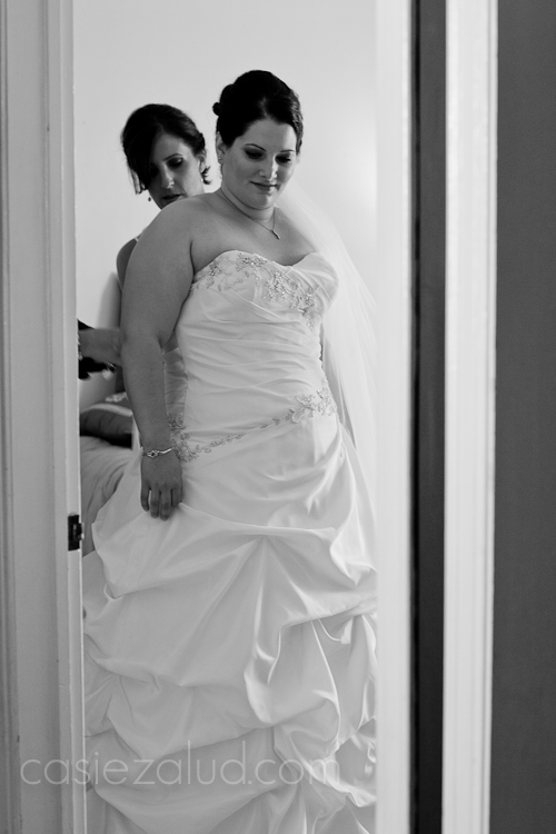the maid of honor tying the bride's dress in the back through a door frame