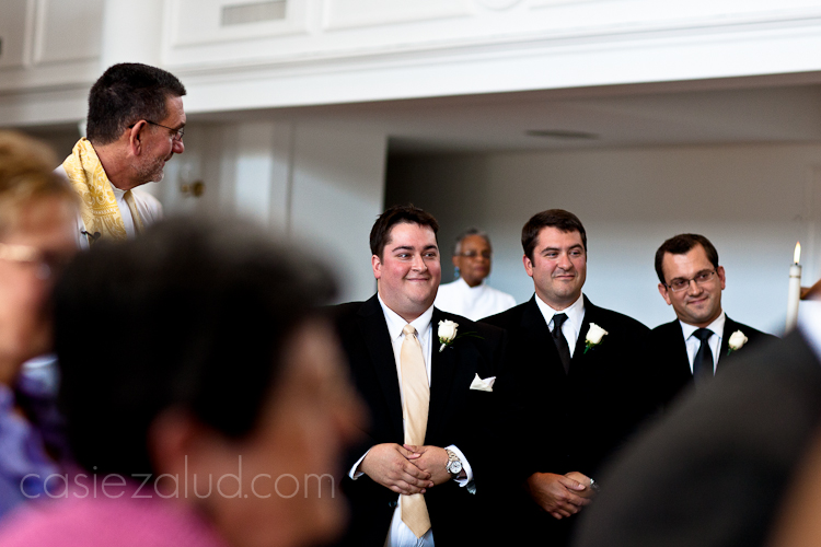 groom and grooms mens smiling as they watch the bride coming down the aisle