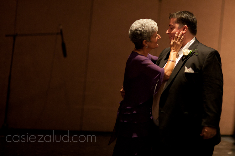 a mother and her son at the end of the mother and son dance at a wedding, she is speaking deeply to him and touching his face