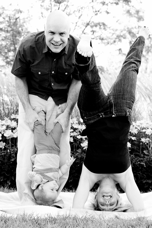 dad holding baby unside down while mom does a headstand