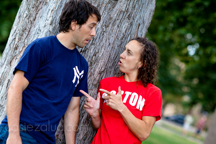 engaged couple: guy wearing a Yankees shirt, girl wearing a Boston shirt saying Boston is number 1