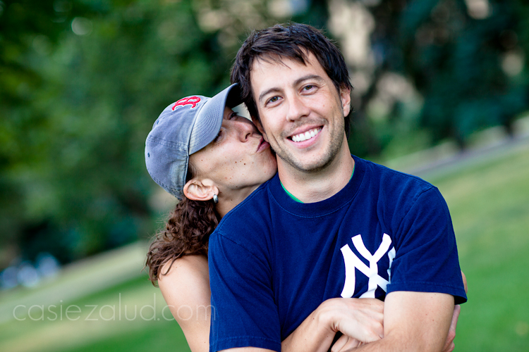 engaged couple: girl wearing a Boston Red Sox hat kissing the guy who is wearing a Yankees t-shirt from behind