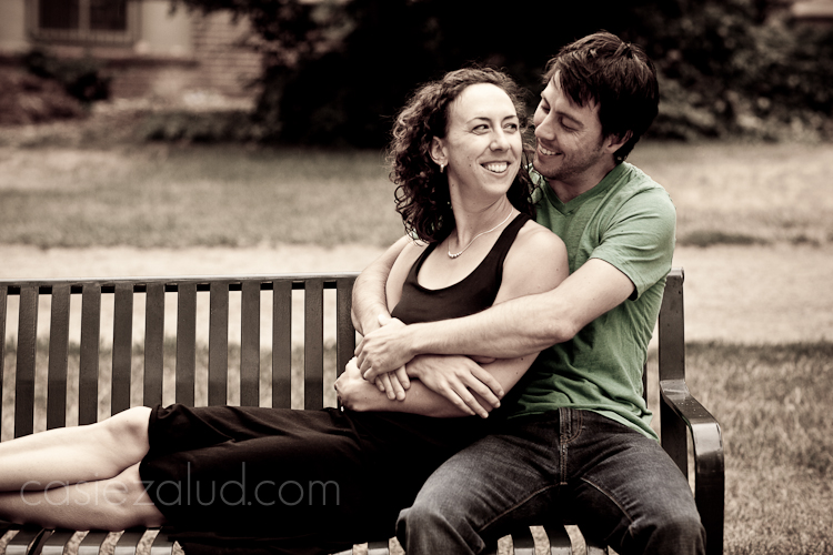 engaged couple on a park bench smiling at each other