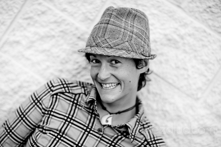 black and white headshot of a woman at an angle with a plaid hat and plaid shirt at an angle.