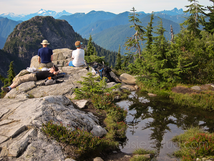 Three people on a mountain top resting. Two are looking out over the view with their backs turned to the camera. One person laying on a rock lounging next to a puddle of water.