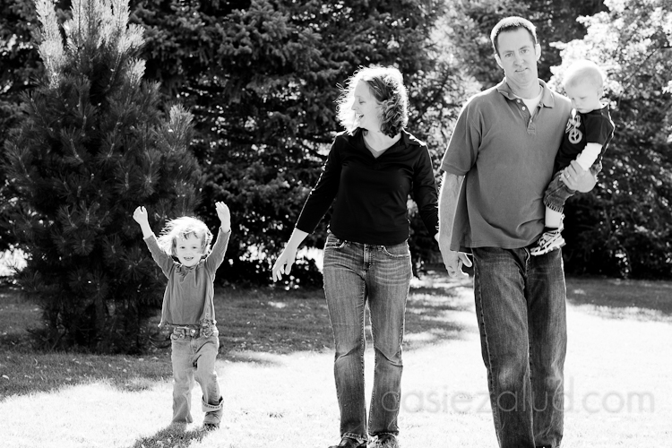 family of four walking towards the camera with three year old holding her hands in the air in black and white