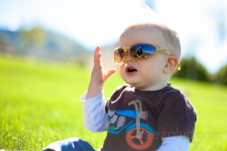 12 month old at the park playing with sunglasses sitting in the grass