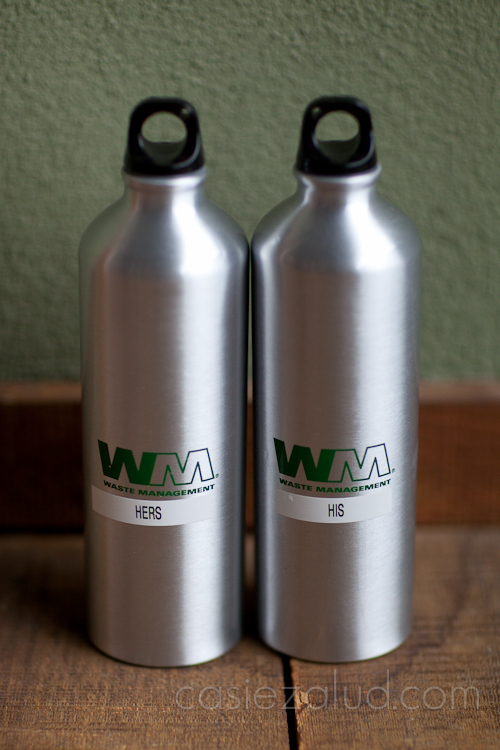two water bottles with waste management logo on them, one says 'hers' the other says 'his'