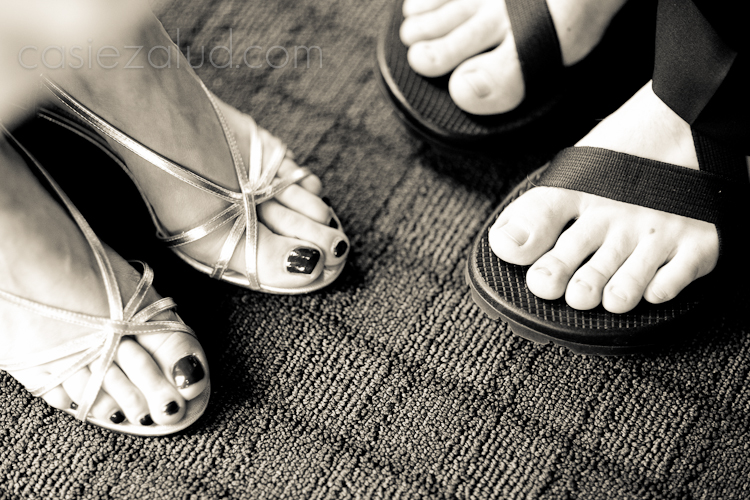 bride and groom's feet, the bride in fancy party shoes with polished toes and the groom in sandals