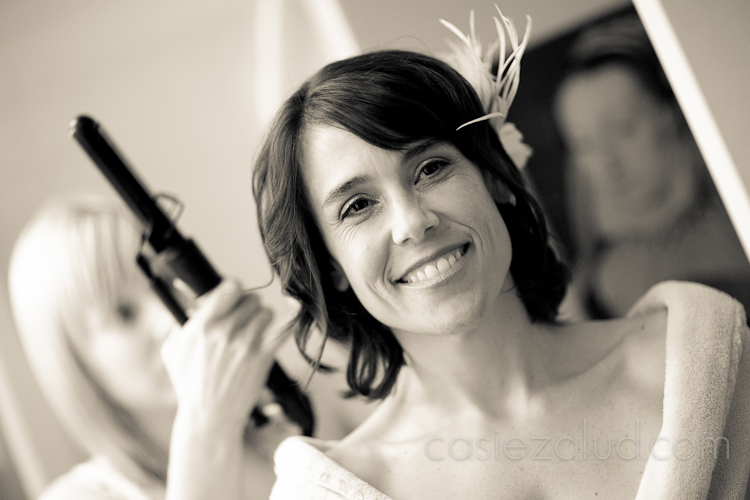 a bride preparing for the wedding getting her hair curled with a curling iron in black and white