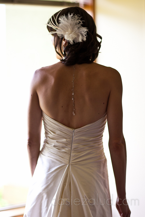 a bride from behind, can see the the back of her dress, her back with a necklace hanging down the back and her feathered hair piece