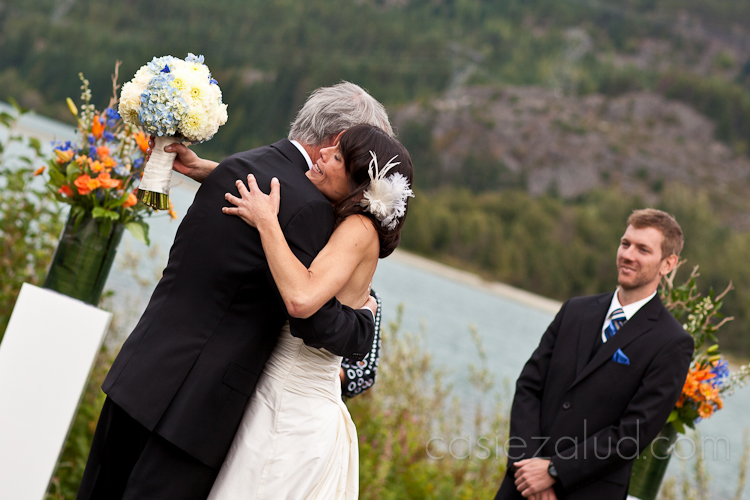 bride hugging her father as he gives her to the groom