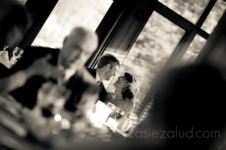 a bride and groom about to kiss at the wedding dinner in black and white