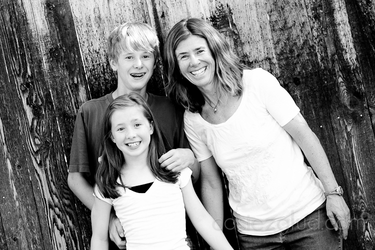 mom, daughter - 10, son - 13, against a fence having fun all smiling in black and white