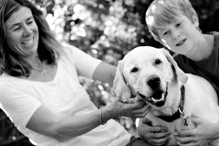 5 year old yellow lab in focus, mom and son out of focus in background in black and white