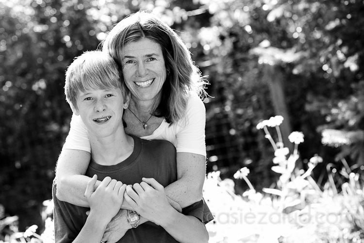 mom hugging 13 year old son from behind, back lit in the garden in black and white