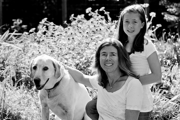 mom, daughter and dog pose in the garden with great back light in black and white