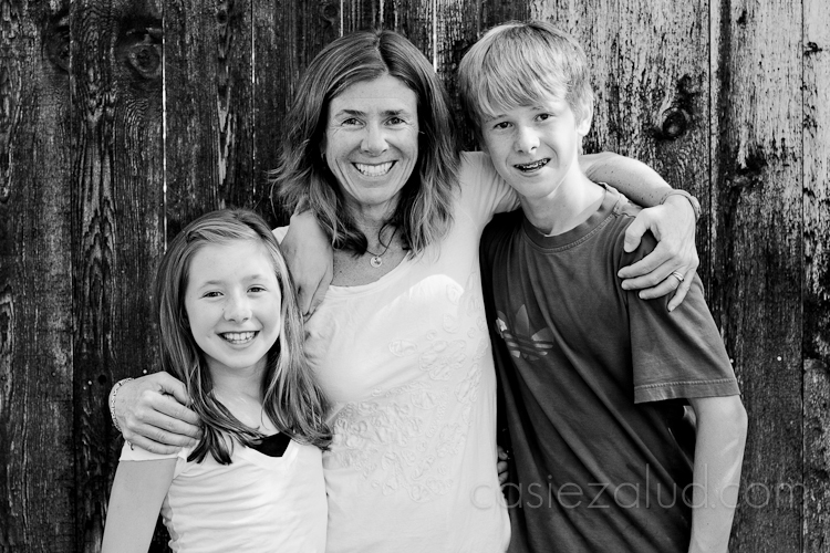 daughter, mom, and son hugging in front of a fence in black and white