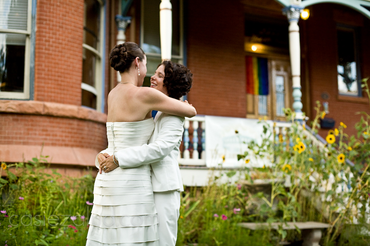 lesbian couple embracing after being married, gay flag in the background