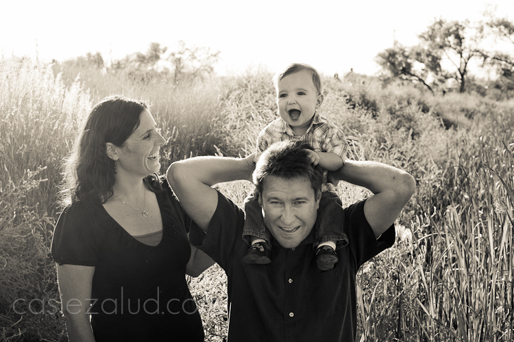 mom, with dad and one year old son on his shoulders at the park in tall grasses