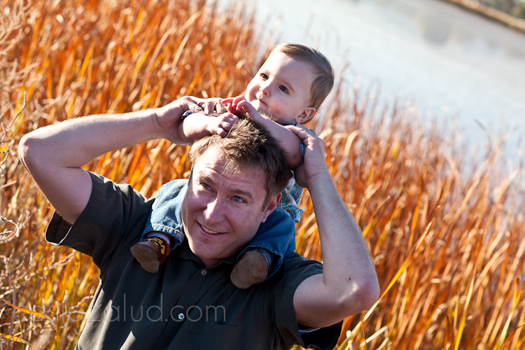 dad and one year old son on his shoulders with orange grassed behind him