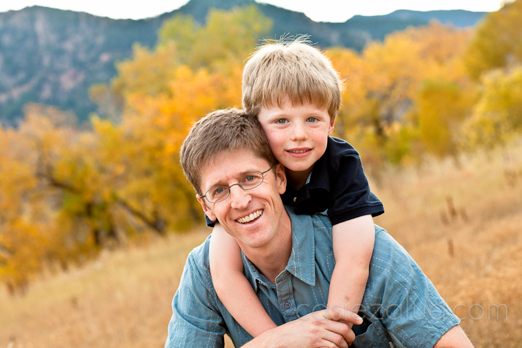 dad sitting on a rock and his six year old son hugging him from behing with golden aspens in the background