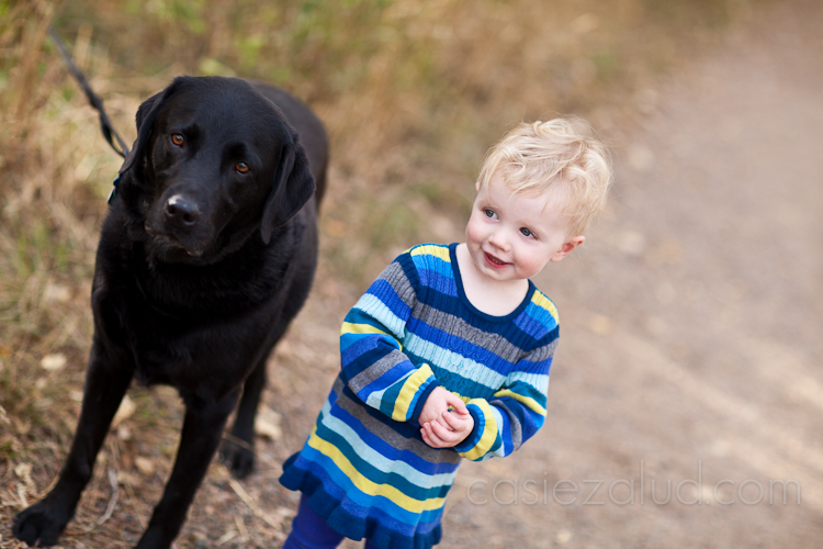 one year old girl standing next to her black lab dog who is looking directly in the camera