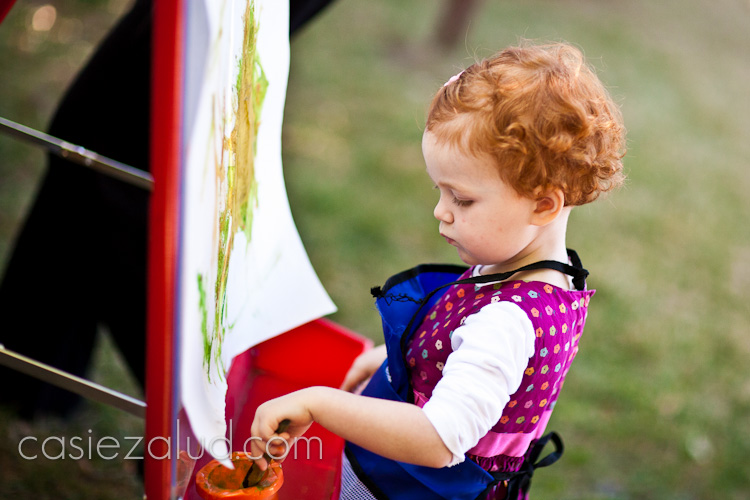 3 year old girl painting outside