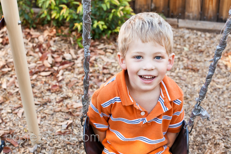 four year old boy sitting on a swing looking up at the camera
