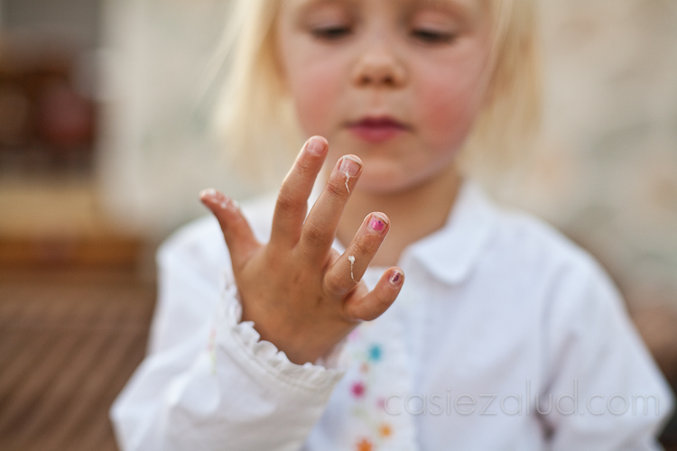 two year old's hand covered in marshmallows, she is out of focus, but the hand is in perfect focus and she is looking at her hand very seriously wondering which finger to lick