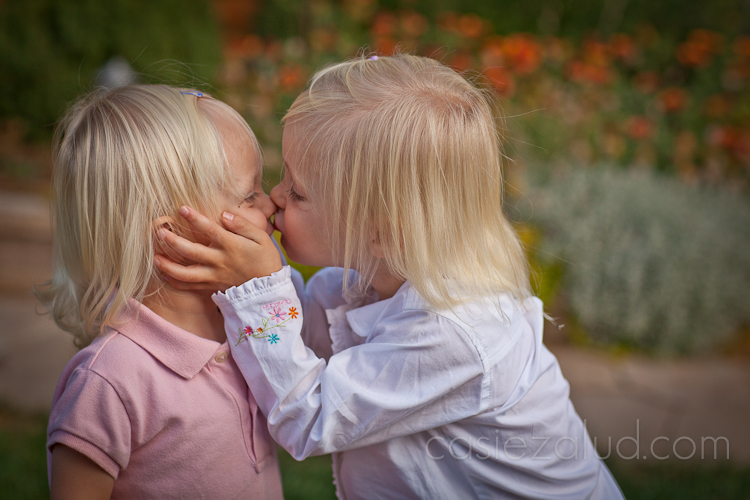 two year old kissing her one year old sister