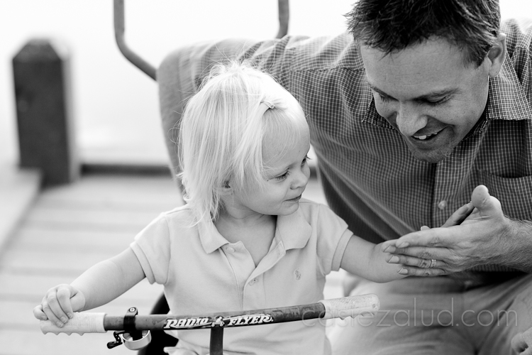 one year old sitting on her tri-cycle giving dad five in black and white