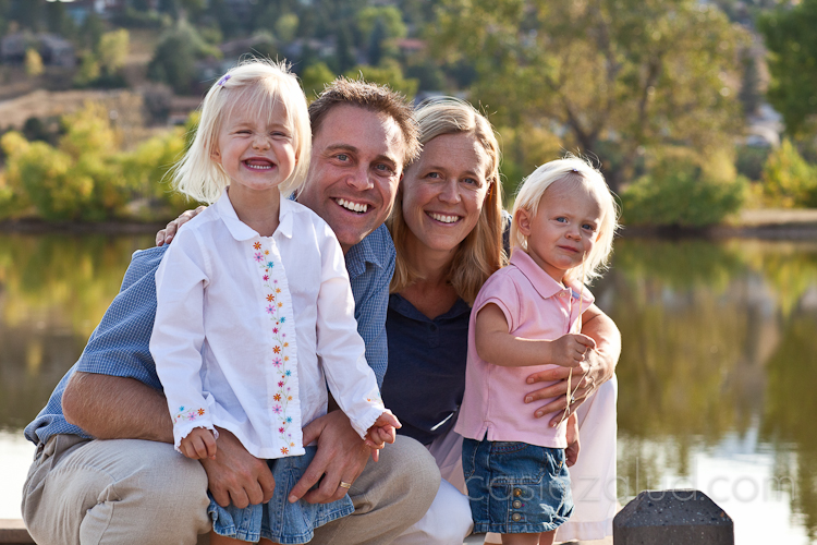 mom, dad, two year old and one year old on a dock at a lake with golden aspens in the background