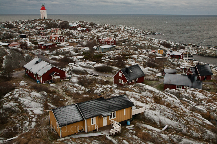 landscape image of a Landsort, a small fishing village on an island in the southern Stockholm archipelago, the rocks and roof tops are covered with frost and the sky is gray