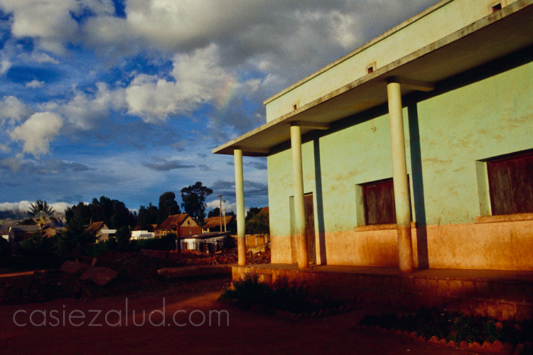 a school in Madagascar at sunset with warm sunlight and a rainbow in the fluffy clouds against a blue sky
