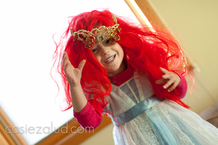 A two year old dressed as Princess Ariel jumping up and down as her red wing and crown falls off and