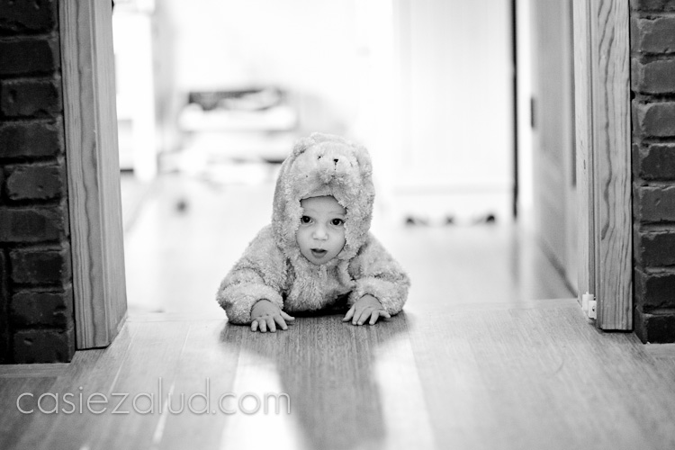a ten month old little boy crawling in a bear costume towards a door jam on wood floor