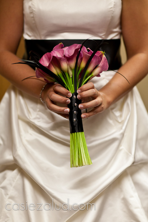 a bride holding her hot pink lily bouquet  in front of her dress