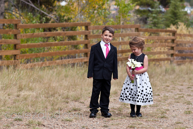 flower girl and ring barer at a wedding. the flower girl is shying away from the camera