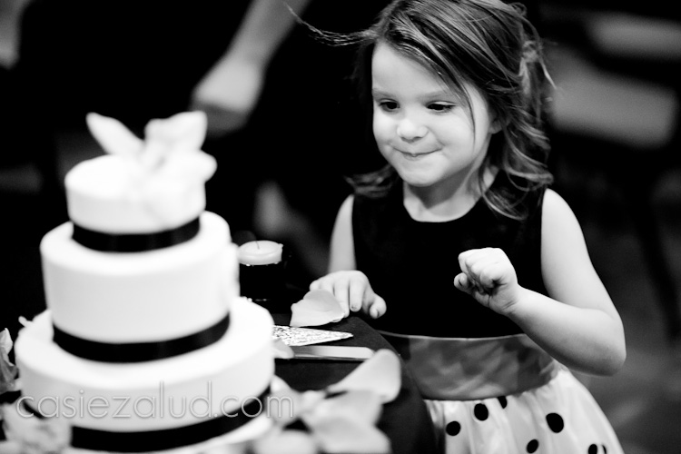 little girl eyeing up a cake on a table, about to stick her finger in for a lick of the frosting