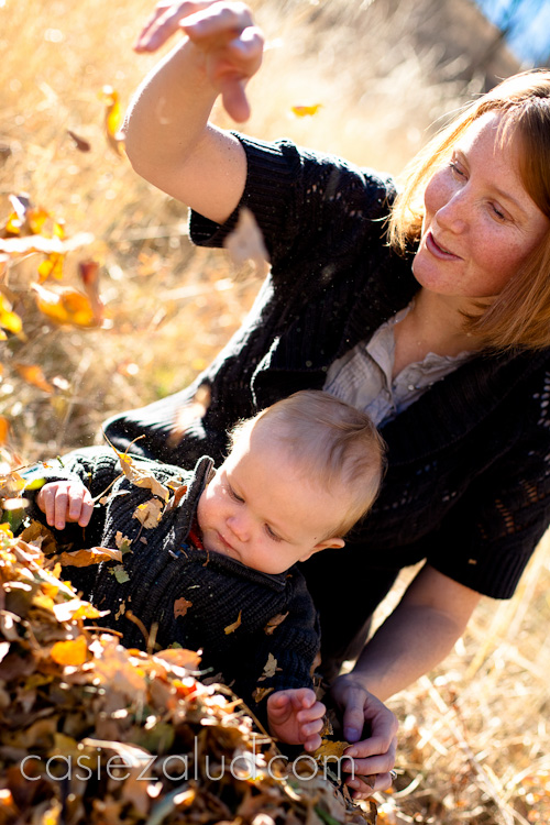 mom and one-year old son playing with leaves in a leaf pile