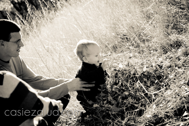 one year old boy tossing leaves around in black and white