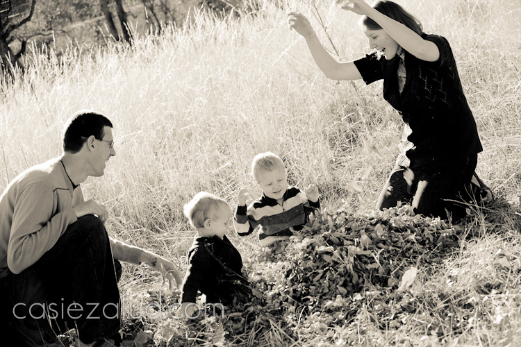family with a two and half year old boy and 1 year old boy throwing leaves in the air in black and white