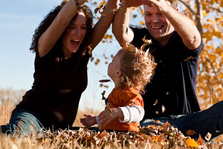 family portraits: mom and dad tossing leaves over a one year old heads